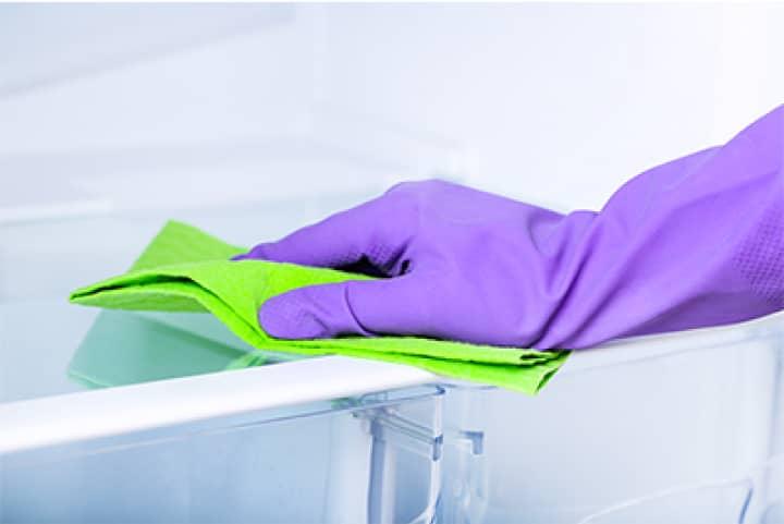 Рука в перчатке протирает тряпкой стол